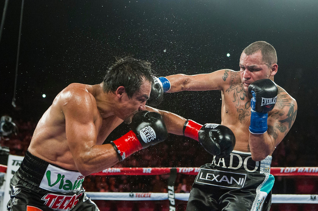 . Mike Alvarado, right, lands a punch against Juan Manuel Márquez, of Mexico, in the fifth round of a WBO welterweight title boxing match at the Forum in Inglewood, Calif., Saturday, May 17, 2014. Márquez won the title.  (AP Photo/Ringo H.W. Chiu)