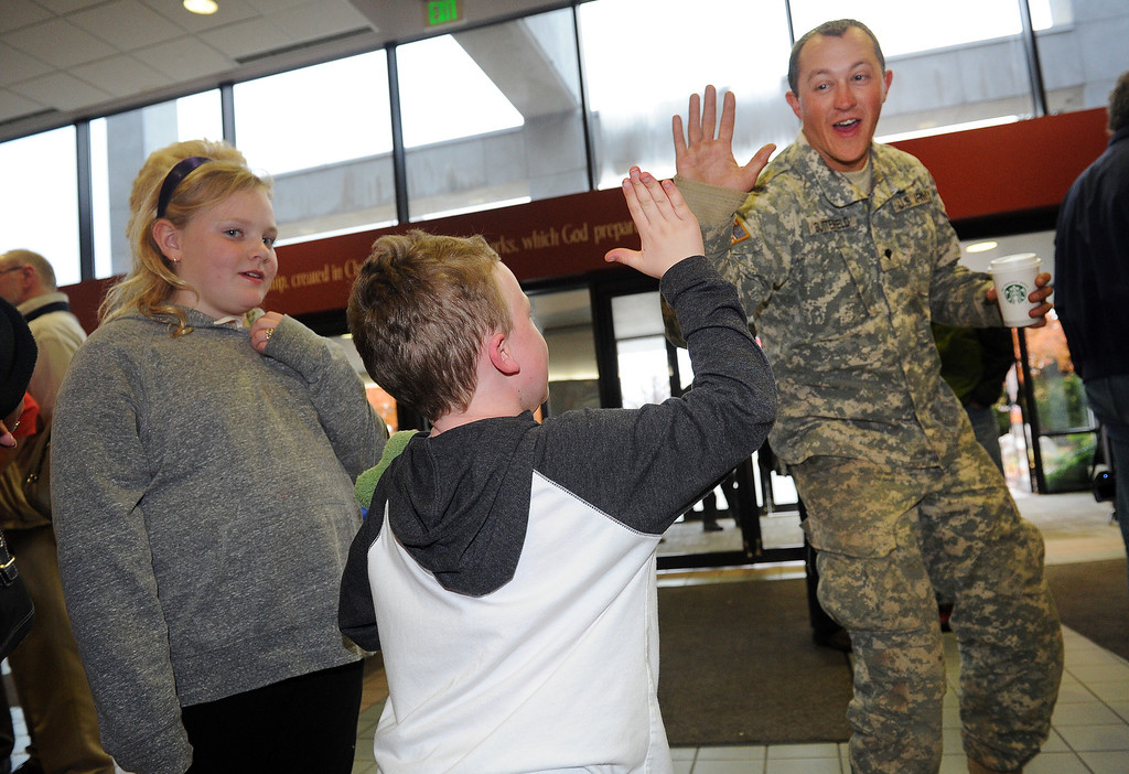 . LONGMONT, CO - OCTOBER 29:   Dallan Butterfield,  of the Utah National Guard, gets a high five from Lyons resident Benjamin Taylor, 7, as they arrive at the Life Bridge Community Church in Longmont, Co on October 29, 2013.  They were coming to be part of a celebration  held to thank members of the military, law enforcement, firefighters and members of Colorado Department of Transportation for all their work during and after the floods.   (Photo By Helen H. Richardson/ The Denver Post)
