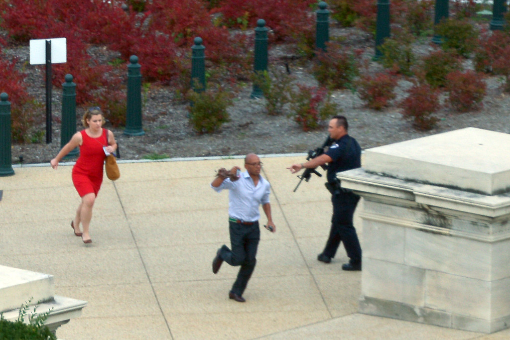 ". People run for cover as police converge to the site of a shooting October 3, 2013 on Capitol Hill in Washington, DC. The US Capitol was placed on security lockdown Thursday after shots were fired outside the complex, senators said. ""Shots fired outside the Capitol. We are in temporary lock down,\"" Senator Claire McCaskill said on Twitter. Police were seen running within the Capitol building and outside as vehicles swarmed to the scene. AFP PHOTO / Mandel NGAN/AFP/Getty Images"