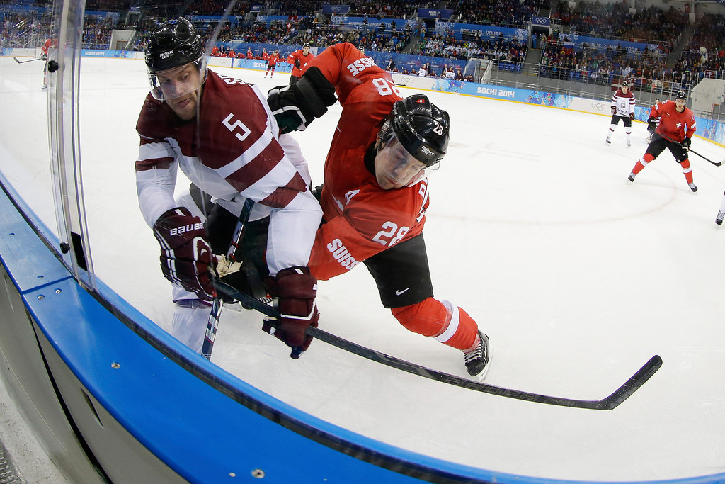 . Switzerland forward Martin Pluss pins Latvia forward Janis Sprukts up against the boards during the first period of the 2014 Winter Olympics men\'s ice hockey game at Shayba Arena, Wednesday, Feb. 12, 2014, in Sochi, Russia. (AP Photo/Matt Slocum)