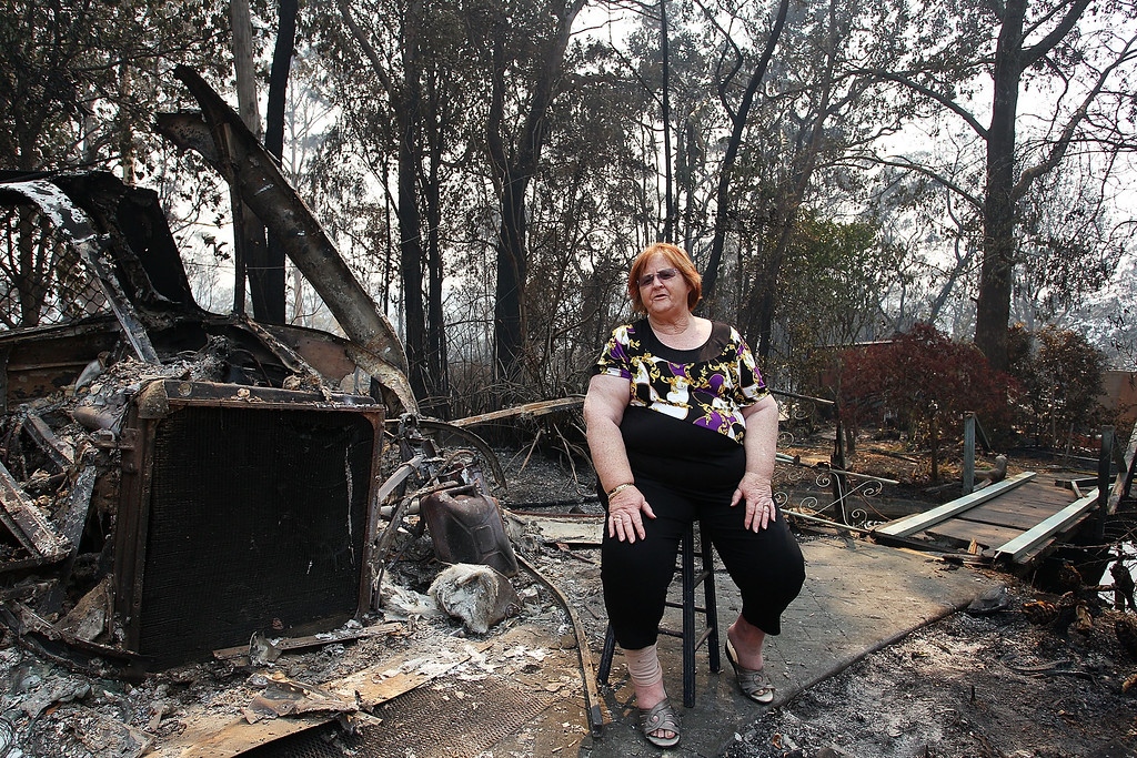 . Sue Dunlop sits in the front yard of her home of 41 years which was destroyed by bushfire on October 21, 2013 in Winmalee, Australia.  (Photo by Lisa Maree Williams/Getty Images)