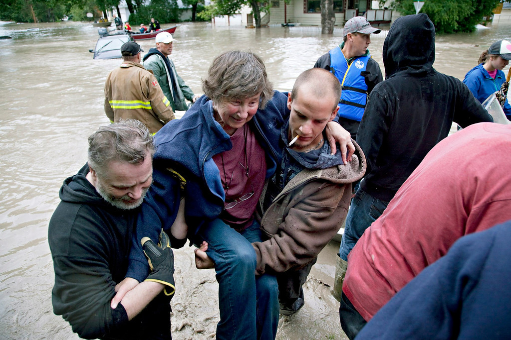 . A woman is rescued from the flood waters in High River, Alberta on Thursday, June 20, 2013 after the Highwood River overflowed its banks. Calgary city officials say as many as 100,000 people could be forced from their homes due to heavy flooding in western Canada, while mudslides have forced the closure of the Trans-Canada Highway around the mountain resort towns of Banff and Canmore. (AP Photo/The Canadian Press, Jordan Verlage)