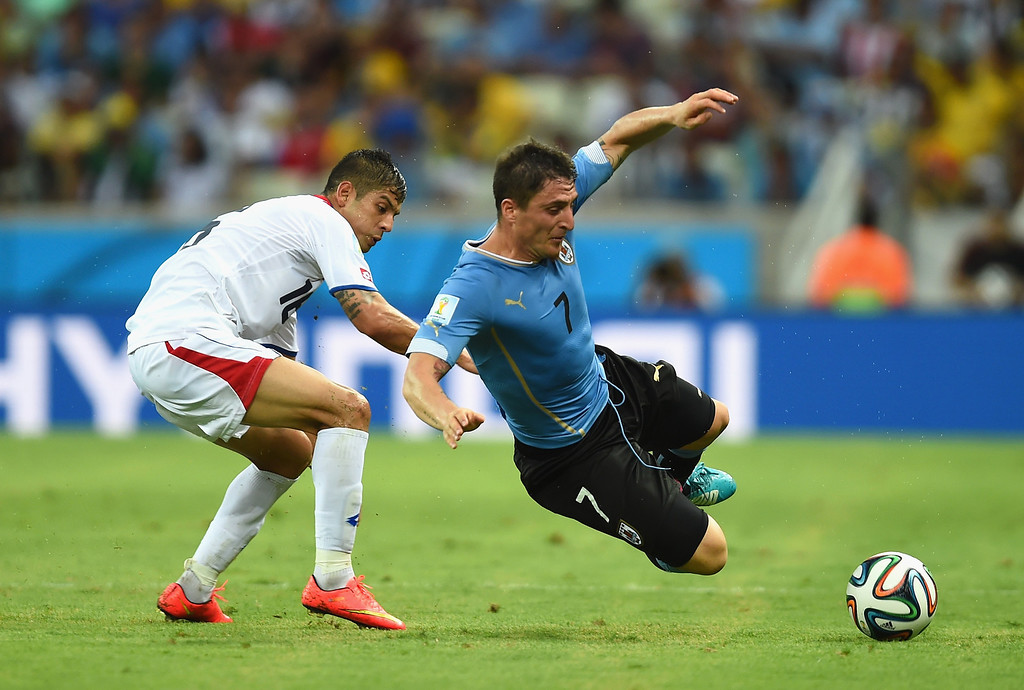 . Cristian Rodriguez of Uruguay falls after a challenge by Cristian Gamboa of Costa Rica during the 2014 FIFA World Cup Brazil Group D match between Uruguay and Costa Rica at Castelao on June 14, 2014 in Fortaleza, Brazil.  (Photo by Jamie McDonald/Getty Images)