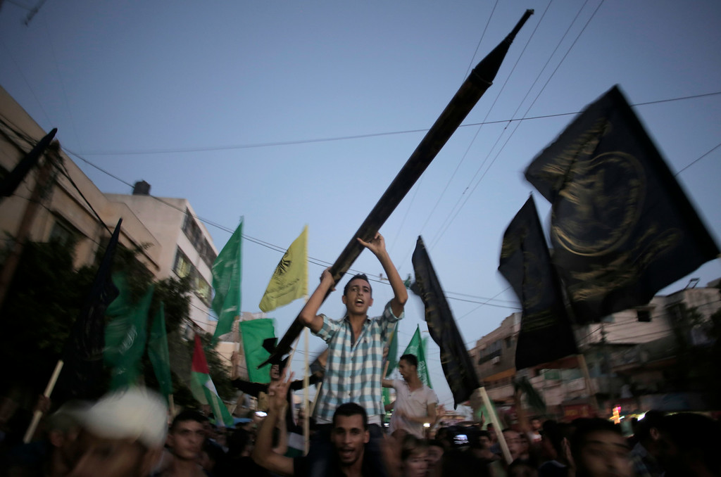 . Palestinians chant slogans one holding a mock Qassam rocket as they celebrate the cease-fire in Gaza City, Tuesday, Aug. 26, 2014. The two sides announced Tuesday that they had agreed to an open-ended cease-fire between Israel and Hamas, after seven weeks of fighting that killed more than 2,200 people, the vast majority Palestinians. (AP Photo/Khalil Hamra)