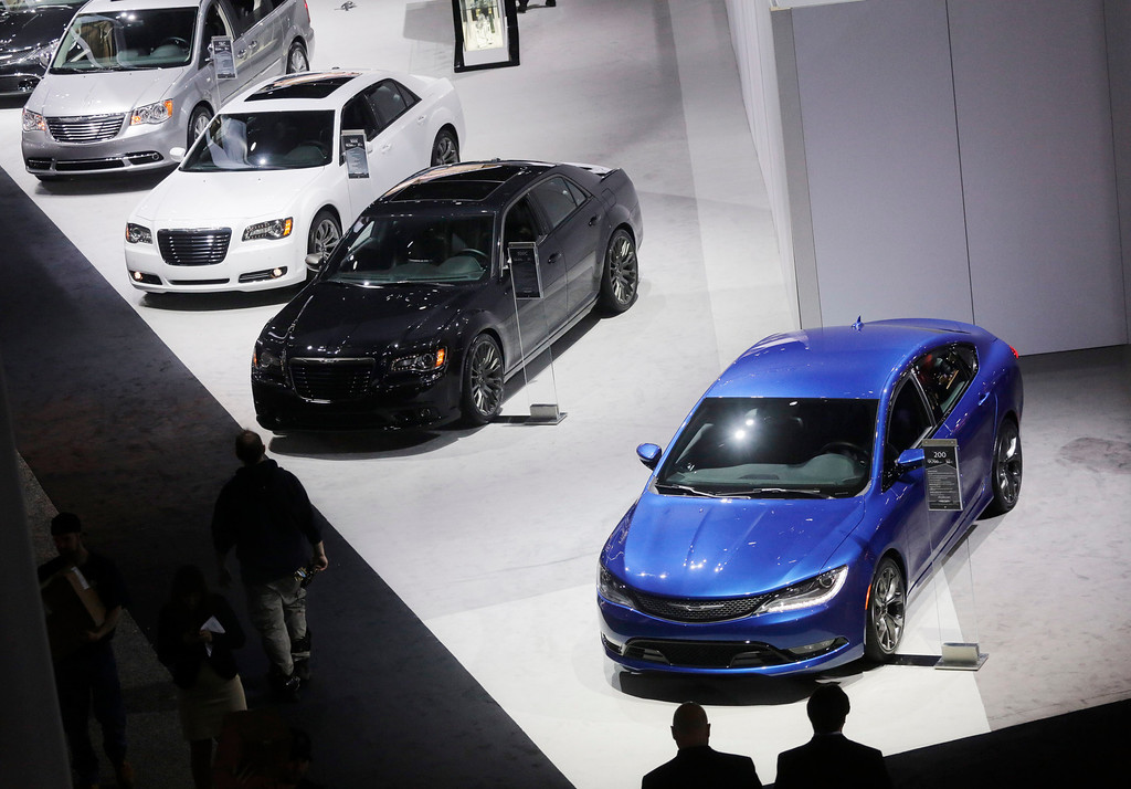 . Members of the media look at Chrysler vehicles on display at the New York International Auto Show, Wednesday, April 16, 2014, in New York. (AP Photo/Mark Lennihan)