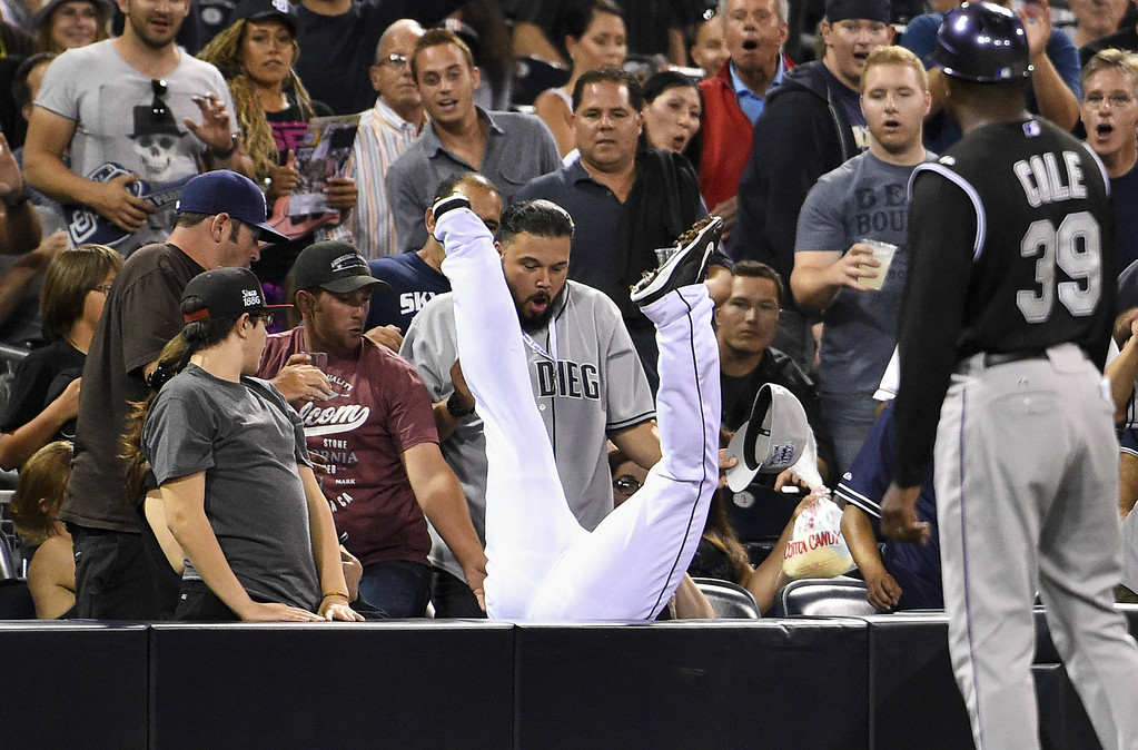 . SAN DIEGO, CA - AUGUST 12:  Chris Nelson #1 of the San Diego Padres flips into the stands as he makes the catch on a foul ball hit by Charlie Blackmon #19 of the Colorado Rockies during the eighth inning of a baseball game at Petco Park August, 12, 2014 in San Diego, California.  (Photo by Denis Poroy/Getty Images)
