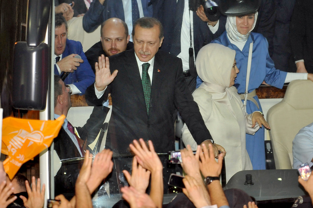 """. Turkish Prime Minister Recep Tayyip Erdogan (L),  wife Emne Erdogan (C) and daugther Sumeye Erdogan (R) are greeted by supporters upon arrival at Ataturk International Airport in Istanbul on June 7, 2013.Turkey\'s Islamic-rooted government apologised to wounded protestors and said it had \""""learnt its lesson\"""" after days of mass street demonstrations that have posed the biggest challenge to Prime Minister Recep Tayyip Erdogan\'s decade in office. Turkish police had on June 1 begun pulling out of Istanbul\'s iconic Taksim Square, after a second day of violent clashes between protesters and police over a controversial development project. What started as an outcry against a local development project has snowballed into widespread anger against what critics say is the government\'s increasingly conservative and authoritarian agenda.  OZAN KOSE/AFP/Getty Images"""