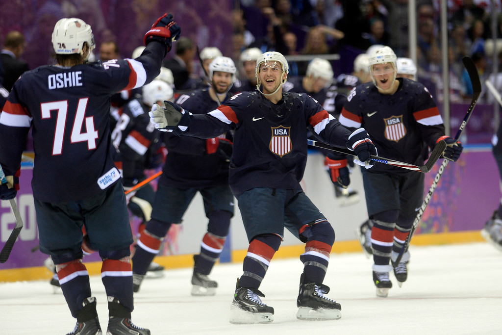 . SOCHI, RUSSIA - FEBRUARY 15: Teammates skate onto the ice to celebrate with T.J. Oshiet (74) of the U.S.A. after he made a game-winning shot on Sergei Bobrovski (72) of the Russia during  the U.S.A.\'s shootout-win at Bolshoy arena. Sochi 2014 Winter Olympics on Saturday, February 15, 2014. (Photo by AAron Ontiveroz/The Denver Post)