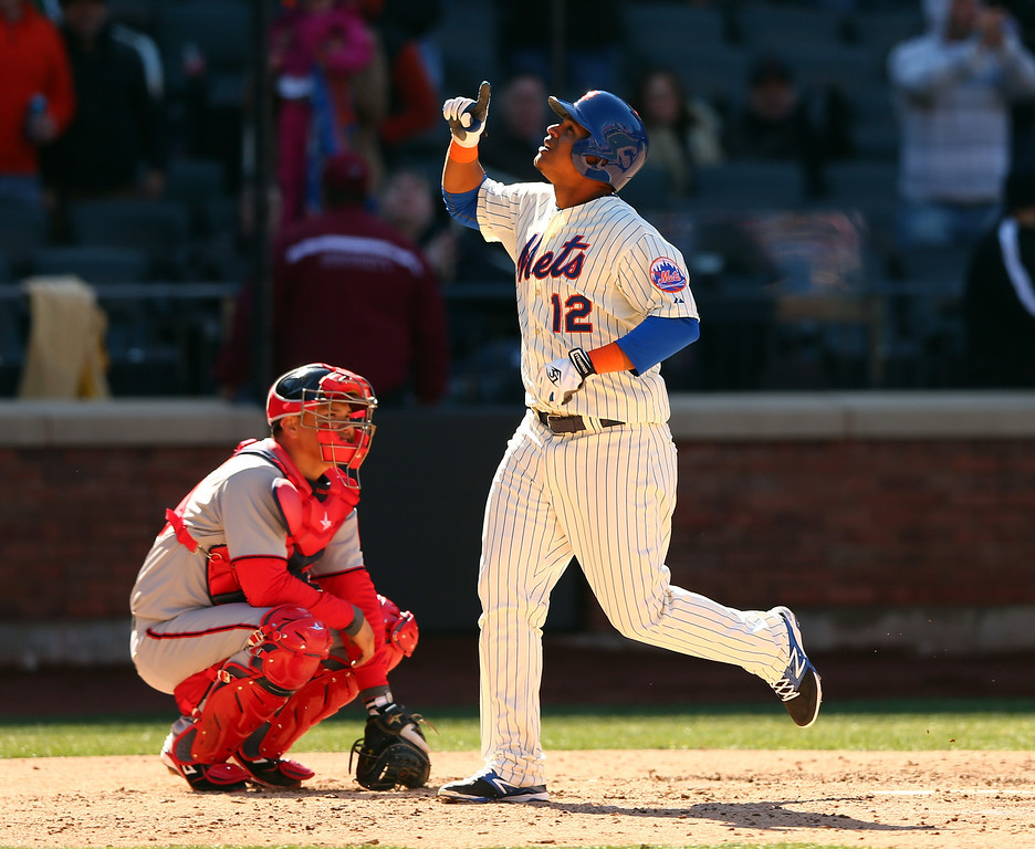 . Juan Lagares #12 of the New York Mets celebrates his solo home run as catcher Wilson Ramos #40 of the Washington Nationals looks on in the eighth inning during Opening Day on March 31, 2014 at Citi Field in the Flushing neighborhood of the Queens borough of New York City.  (Photo by Elsa/Getty Images)