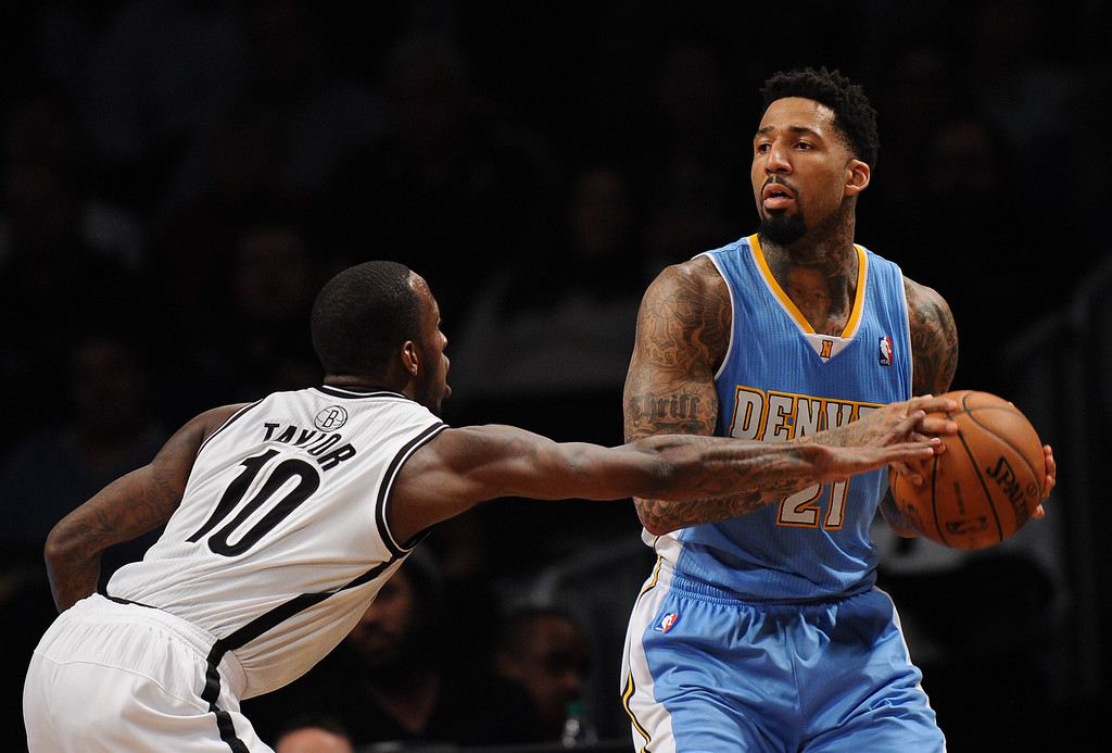 . NEW YORK, NY - DECEMBER 03:  Wilson Chandler #21 of the Denver Nuggets looks for a pass with pressure from Tyshawn Taylor #10 of the Brooklyn Nets during the second half at Barclays Center on December 3, 2013 in the Brooklyn borough of New York City. The Nuggets defeat the Nets 111-87. (Photo by Maddie Meyer/Getty Images)