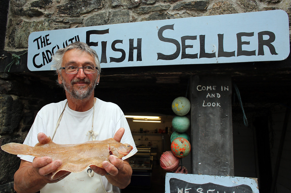 . CADGWITH, ENGLAND - SEPTEMBER 05:  Cadgwith fisherman and proprietor of the Cadgwith Fish Seller fish shop, Jonathan Fletcher poses for a photograph with a locally caught fish, prior to the final fortnightly fishing competition of the year in Cadgwith on September 5, 2013 in Cornwall, England. The summertime competition to catch the heaviest fish of a chosen type, (for this final the fish was bass) allows locals and visitors the chance to fish for fun and a cash prize, with the catch cooked in a pot at the end of the night on some occasions. Set on the Lizard peninsula in Cornwall, the village of Cadgwith, which was established in medieval times, owes its existence to the fishing industry. However, whilst fishing remains an important part of village life today, tourism is also now a major source of income for the inhabitants. (Photo by Matt Cardy/Getty Images)