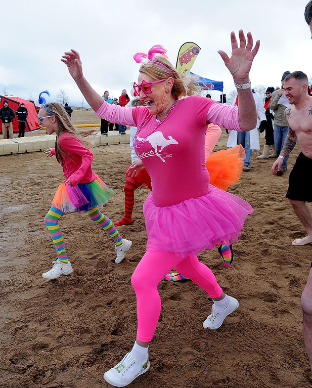 . Leonie Walker, a first timer, runs in to the icy water to do one of the things on her bucket list.The 31st annual Boulder Polar Plunge, at the Boulder Reservoir on New Year�s Day, to help the Boulder County AIDS Project and connectBCAP.  Cliff Grassmick/Daily Camera