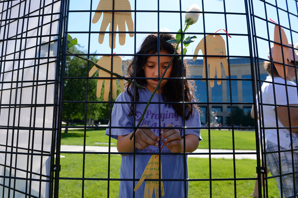 . AURORA, CO - JULY 20:  Kairi Fahlenkamp, 10, attaches a paper cut-out of a hand with a personal message on it, onto the �healing wall� at the 7/20 Day of Remembrance 2013 at the Aurora Municipal Center Saturday morning, July 20, 2013. Fahlenkamp\'s cousin, Veronica Moser, then 6-years-old, was killed in the theater shooting rampage July 20, 2012. Over 200 people attended the service in honor of the 12 people killed and over 60 people injured in last years Aurora theater shooting. The memorial service, marking the one-year anniversary of the tragic shooting,  included prayer, songs and speeches from local officials and the Governor of Colorado, John Hickenlooper. (Photo By Andy Cross/The Denver Post)