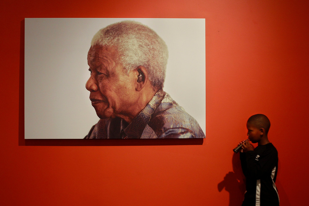 . A young boy walks in front of a portrait of the late South African president Nelson Mandela at the Nelson Mandela Foundation in Johannesburg, South Africa, 07 December 2013. People all over the world were paying tribute to Nelson Mandela, as they reflected on his long walk to freedom and his enduring legacy. The former South African president and anti-Apartheid icon died after a long illness 05 December at the age of 95.  EPA/DAI KUROKAWA