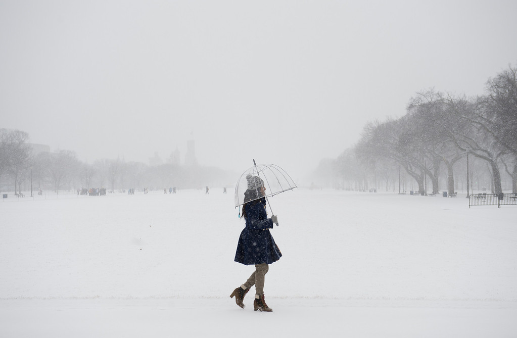 . A woman walks along the National Mall in Washington, DC, January 21, 2014, as snow falls during a storm. The northeastern United States hunkered down Tuesday for a major snowstorm that forecasters warned could leave as much as one foot (30 centimeters) of snow in some places. Downtown Washington fell virtually silent after the federal government, seeing the swift-moving cold front approaching, closed its doors and told civil servants to stay home. Many offices and schools followed suit, as 20 mile (32 kilometer) per hour winds whipped the falling snow through the unusually quiet streets. Enough snow was expected to fall on the US capital to turn the evening rush hour into a Beltway traffic nightmare, as the storm churned its way into New York and the northeastern New England states. AFP PHOTO / Saul LOEB/AFP/Getty Images