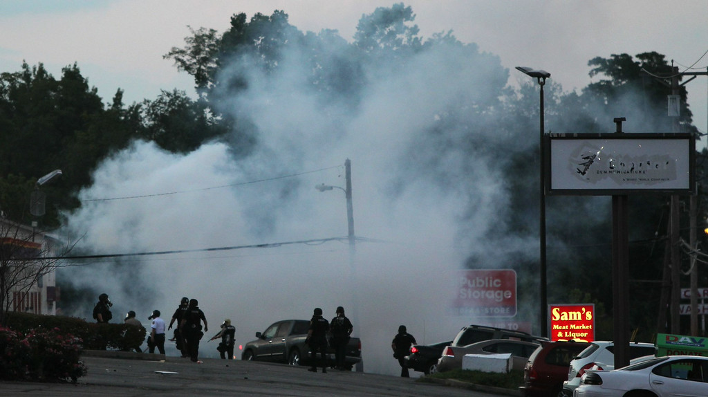 . Tactical officers fire tear gas on Monday, Aug. 11, 2014, in Ferguson, Mo. Authorities in Ferguson used tear gas and rubber bullets to try to disperse a large crowd Monday night that had gathered at the site of a burned-out convenience store damaged a night earlier, when many businesses in the area were looted. (AP Photo/St. Louis Post-Dispatch, Robert Cohen)