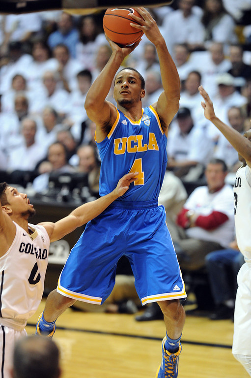 . Norman Powell of UCLA scoots past Askia Booker of CU during the first half of the January 16, 2014 game in Boulder.  (Cliff Grassmick/Daily Camera)