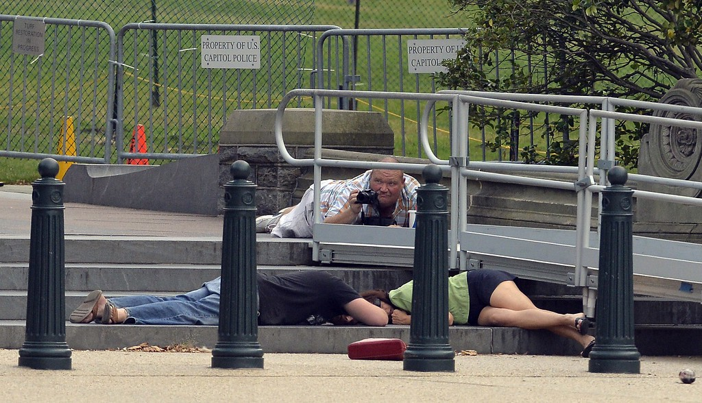 ". People take cover as gun shots were being heard at the US Capitol in Washington, DC, on October 3, 2013. The US Capitol was placed on security lockdown Thursday after shots were fired outside the complex, senators said. ""Shots fired outside the Capitol. We are in temporary lock down,\"" Senator Claire McCaskill said on Twitter. Police were seen running within the Capitol building and outside as vehicles swarmed to the scene. AFP Photo/Jewel SAMAD/AFP/Getty Images"