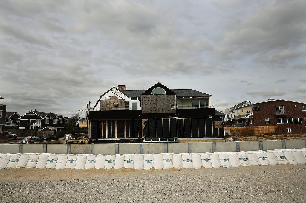 . A newly built protective sea wall stands in front of beachfront property in the Belle Harbor neighborhood on October 9, 2013 in the Queens borough of New York City. Nearly one year after Hurricane Sandy devastated much of the area with severe flooding and wind damage, the Rockaways and Belle Harbor   have made great headway with rebuilding and renovations to the iconic beach community. Despite the progress, the community is still reeling from the destruction of the world famous boardwalk and the closure of many area businesses. Hurricane Sandy made landfall on October 29 near Brigantine, New Jersey and affected 24 states from Florida to Maine and cost the country an estimated $65 billion.  (Photo by Spencer Platt/Getty Images)