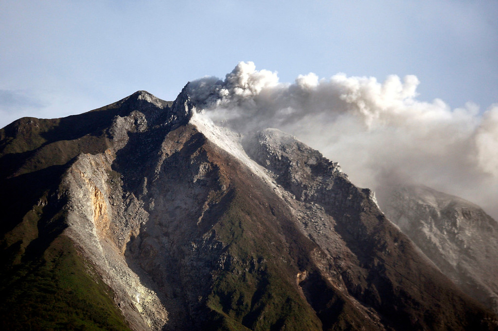 . Mount Sinabung spews volcanic materials from its crater as seen from Karo, North Sumatra, Indonesia, Monday, Sept. 16, 2013. Thousands of people have been evacuated from their homes after the volcano erupted Sunday.   (AP Photo/Binsar Bakkara)