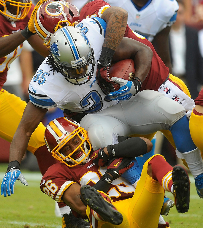 . Detroit Lions running back Joique Bell is pulled to the ground by Washington Redskins cornerback Josh Wilson (26) during the first half of a NFL football game in Landover, Md., Sunday Sept. 22, 2013. (AP Photo/Richard Lipski)