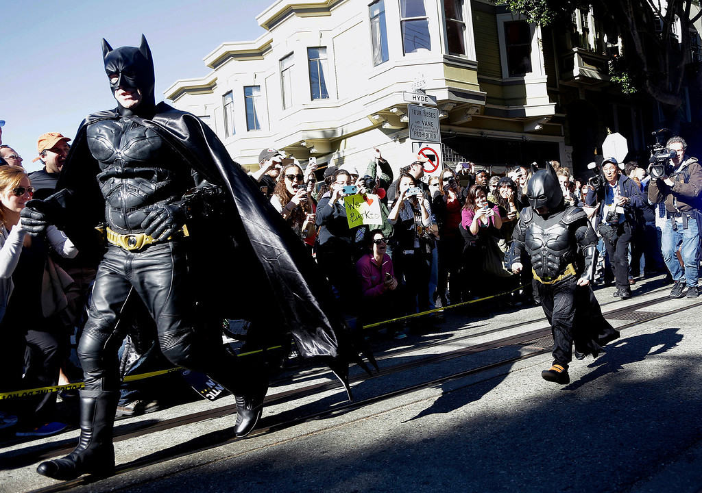 """. Miles Scott, dressed as Batkid, right, runs with Batman after saving a damsel in distress in San Francisco, Friday, Nov. 15, 2013. San Francisco turned into Gotham City on Friday, as city officials helped fulfill Scott\'s wish to be \""""Batkid.\"""" Scott, a leukemia patient from Tulelake in far Northern California, was called into service on Friday morning by San Francisco Police Chief Greg Suhr to help fight crime, The Greater Bay Area Make-A-Wish Foundation says. (AP Photo/Jeff Chiu)"""
