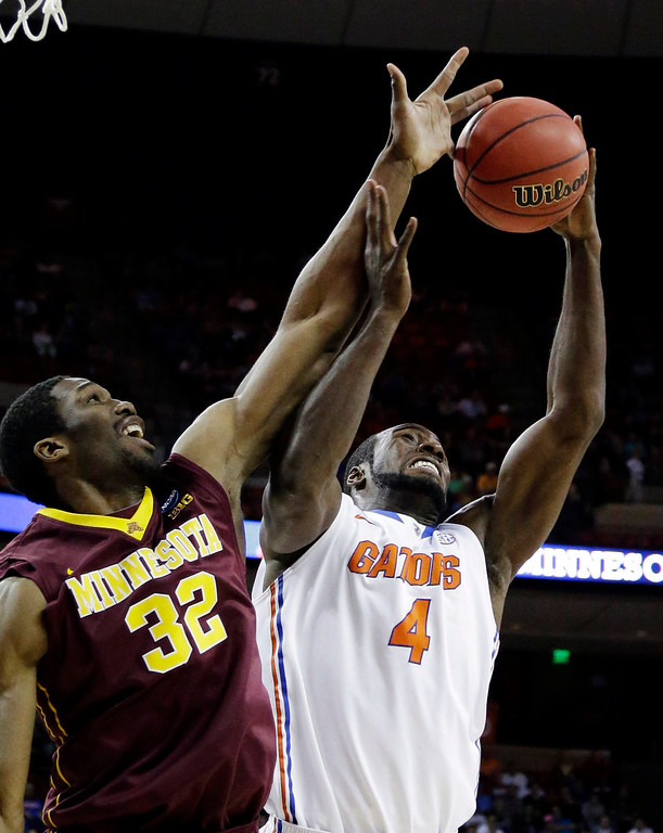 . Minnesota\'s Trevor Mbakwe (32) and Florida\'s Patric Young (4) reach for a rebound during the first half of a third-round game of the NCAA college basketball tournament, Sunday, March 24, 2013, in Austin, Texas. (AP Photo/David J. Phillip)
