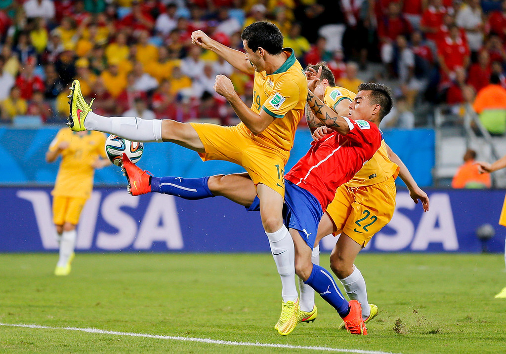 . Chile\'s Eduardo Vargas, center, is challenged by Australia\'s Alex Wilkinson, right, and Ryan McGowan during the group B World Cup soccer match between Chile and Australia in the Arena Pantanal in Cuiaba, Brazil, Friday, June 13, 2014.  (AP Photo/Frank Augstein)
