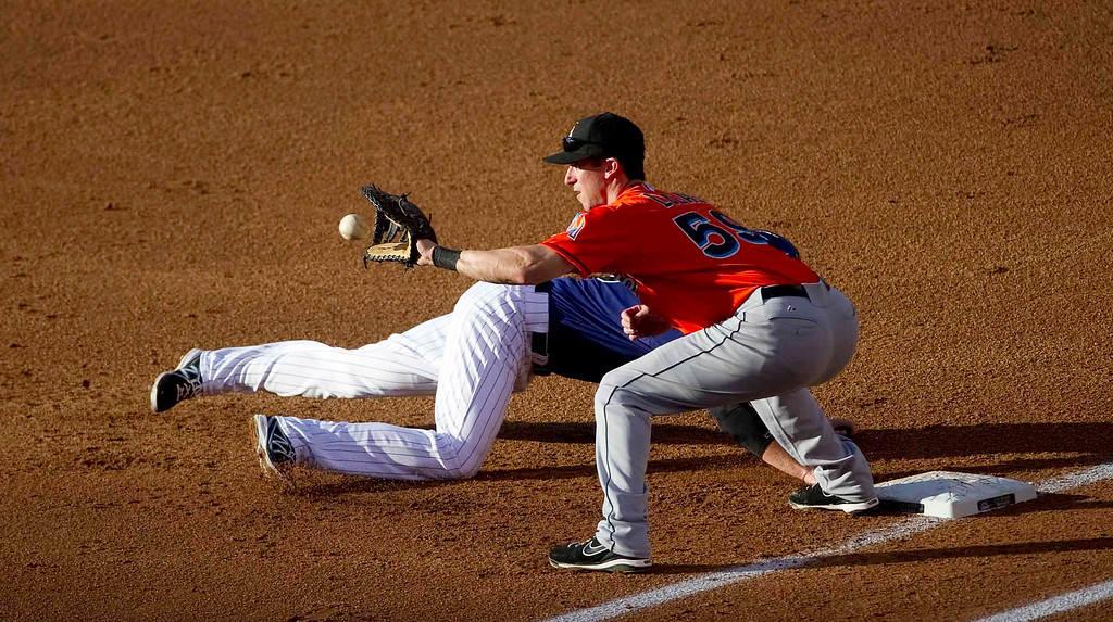. Miami Marlins\' Ed Lucas #59 attempts to beat #9 Colorado Rockies\' DJ LeMahieu #9 to first base during the second inning of a Major League Baseball game between the Miami Marlins and the Colorado Rockies on July 22, 2013 at Coors Field in Denver. (Photo By Grant Hindsley/The Denver Post)