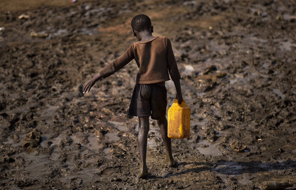 . A displaced child struggles to carry a container of drinking water obtained from a truck across a slippery muddy patch of ground at a United Nations compound which has become home to thousands of people displaced by the recent fighting, in the capital Juba, South Sudan, Sunday, Dec. 29, 2013. Some 25,000 people live in two hastily arranged camps for the internally displaced in Juba and nearly 40,000 are in camps elsewhere in the country, two weeks after violence broke out in the capital and a spiraling series of ethnically-based attacks coursed through the nation, killing at least 1,000 people. (AP Photo/Ben Curtis)