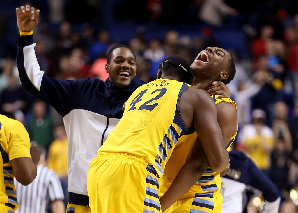 . LEXINGTON, KY - MARCH 23:  Davante Gardner #54 and Chris Otule #42 of the Marquette Golden Eagles celebrate with teammates after defeating the Butler Bulldogs during the third round of the 2013 NCAA Men\'s Basketball Tournament at Rupp Arena on March 23, 2013 in Lexington, Kentucky.  (Photo by Andy Lyons/Getty Images)