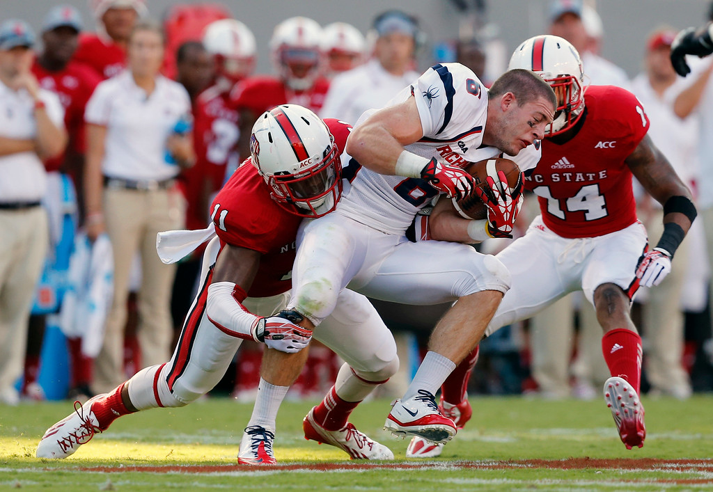 . Richmond wide receiver Ben Edwards (6) after losing his helmet, is tackled by N.C. State\'s cornerback Juston Burris (11) and safety Jarvis Byrd (14) during the first half of an NCAA college football game, Saturday, Sept. 7, 2013 in Raleigh, N.C. (AP Photo/The News & Observer, Ethan Hyman)
