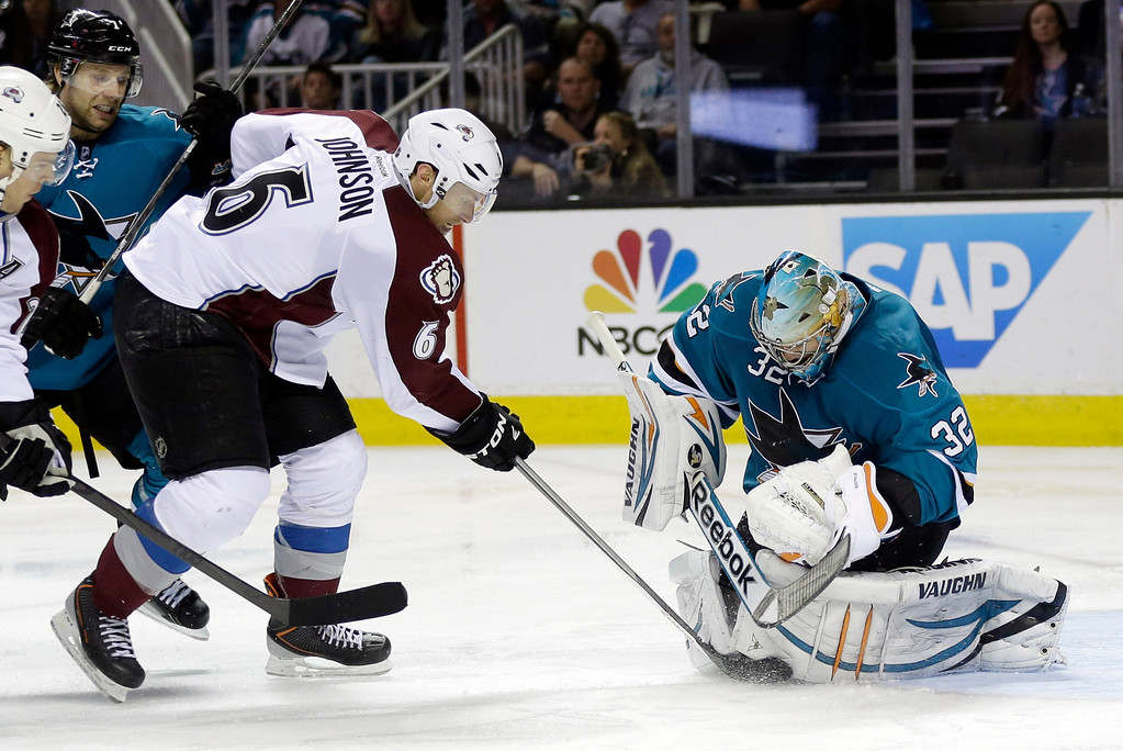 . San Jose Sharks goalie Alex Stalock, right, stops a shot from Colorado Avalanche\'s Erik Johnson (6) during the second period of an NHL hockey game on Friday, April 11, 2014, in San Jose, Calif. (AP Photo/Marcio Jose Sanchez)