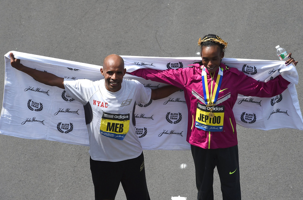 . Men\'s Elite division winner Meb Keflezighi(L) of the US and Women\'s Elite Division winner Rita Jeptoo of Kenya pose for photographers after running the 118th Boston Marathon in Boston, Massachusetts April 21, 2014 .  AFP PHOTO / Timothy A. CLARY/AFP/Getty Images