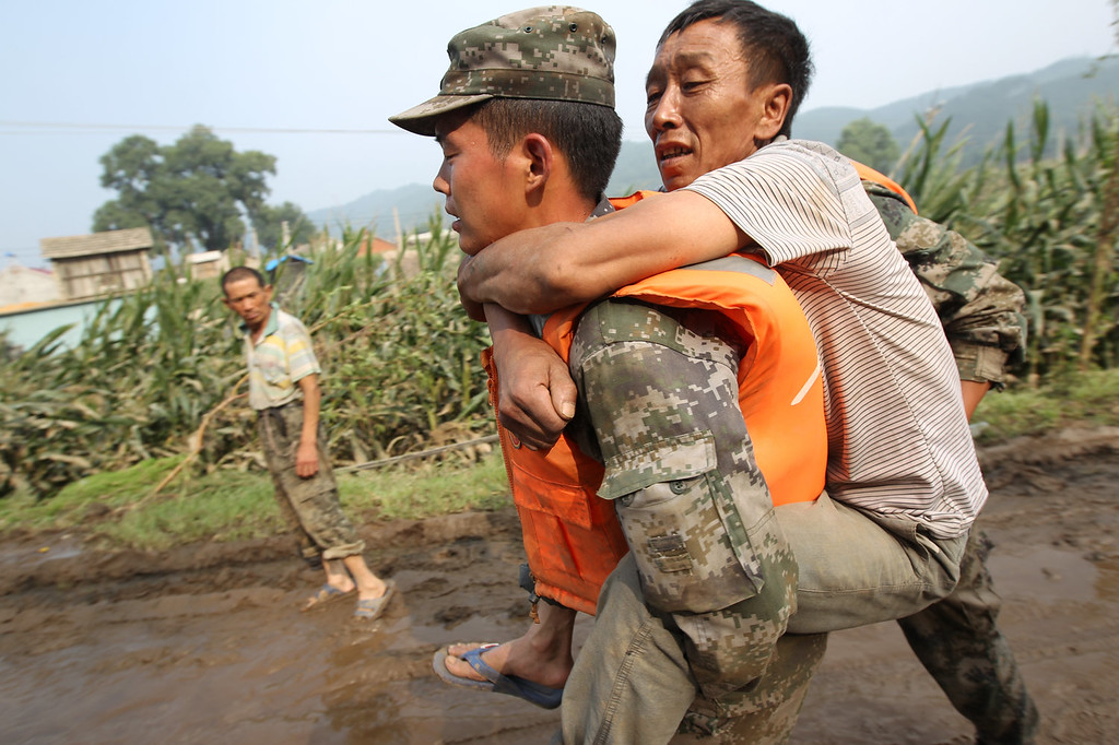 . A rescuer walks with a man on his back after a heavy rain hit on August 18, 2013 in Fushun, China. 32 are missing and 15 are dead after a torrential rain hit Liaoning Province of China.  (Photo by ChinaFotoPress/ChinaFotoPress via Getty Images)