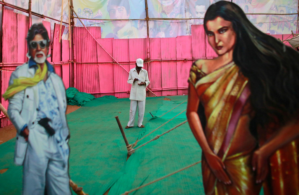 ". An employee of Anoop Touring Talkies, a travelling tent cinema company, stands between cut-outs of Bollywood actors Amitabh Bachchan and Rekha in Mumbai April 23, 2013. Indian cinema marks 100 years since Dhundiraj Govind Phalke\'s black-and-white silent film ""Raja Harishchandra\"" (King Harishchandra) held audiences spellbound at its first public screening on May 3, 1913, in Mumbai. Indian cinema, with its subset of Bollywood for Hindi-language films, is now a billion-dollar industry that makes more than a thousand films a year in several languages. It is worth 112.4 billion rupees (over $2 billion) and leads the world in terms of films produced and tickets sold. Picture taken April 23, 2013. REUTERS/Danish Siddiqui"