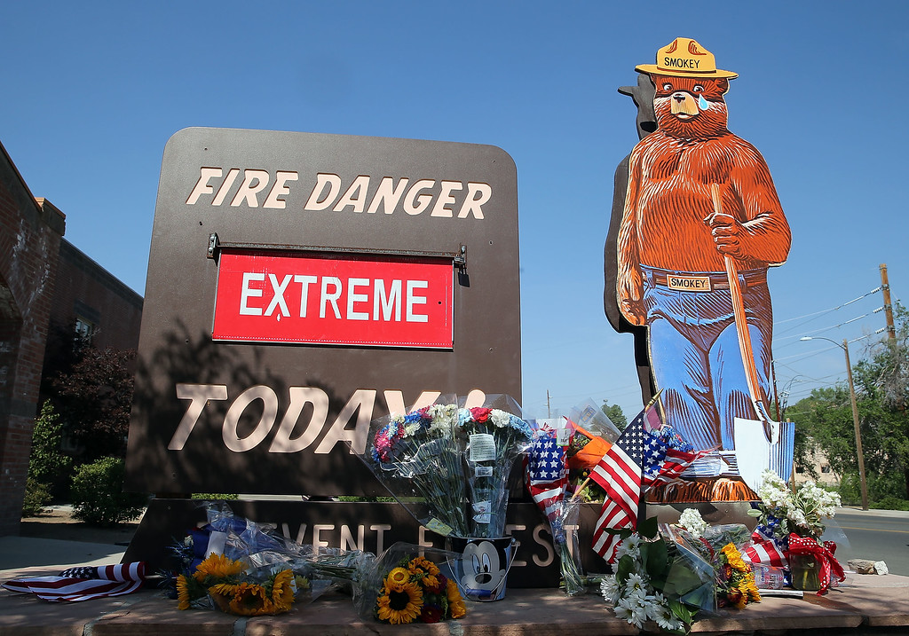 ". American flags and flowers adorn a ""Extreme\"" fire danger warning outside of Fire station 1 on July 2, 2013 in Prescott, Arizona.  (Photo by Christian Petersen/Getty Images)"
