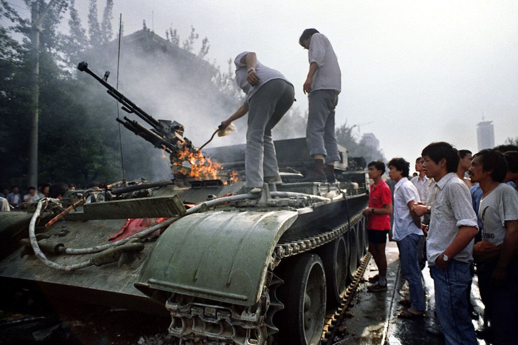 ". Chinese residents check a burning armored personnel carrier which was set on fire by rioters fighting back when the army opened fire on the civilians on June 4, 1989 near Tiananmen Square in Beijing. On the night of 03 and 04 June 1989, Tiananmen Square sheltered the last pro-democracy supporters. A series of pro-democracy protests was sparked by the April 15 death of former communist party leader Hu Yaobang. In a show of force, China leaders vented their fury and frustration on student dissidents and their pro-democracy supporters. Several hundred people were killed and thousands wounded when soldiers moved on Tiananmen Square during a violent military crackdown ending six weeks of student demonstrations, known as the Beijing Spring movement. According to Amnesty International, five years after the crushing of the Chinese pro-democracy movement, ""thousands\"" of prisoners remained in jail. TOMMY CHENG/AFP/Getty Images"