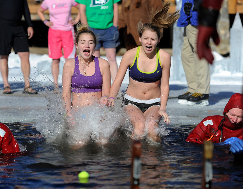 . Dozens joined in for the 6th annual Evergreen Lake Plunge on New Years Day, 2013, where only the very brave jumped, dove, and even performed a belly flop into the icy waters of Evergreen Lake. Friends from Evergreen Kiira Antenucci, 14, left, and Annie Miller, 15, decided to go in as team. Kathryn Scott Osler, The Denver Post