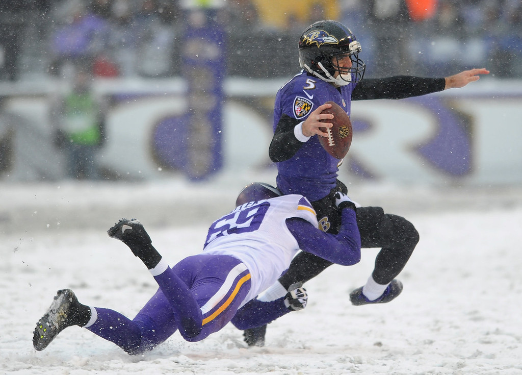 . Baltimore Ravens quarterback Joe Flacco is tackled by Minnesota Vikings defensive end Jared Allen as he rushes the ball in the first half of an NFL football game, Sunday, Dec. 8, 2013, in Baltimore. (AP Photo/Gail Burton)