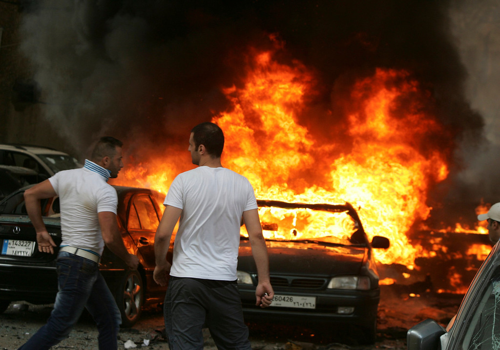 . Men are seen near burning cars at the site of an explosion in Beirut\'s southern suburbs July 9, 2013. REUTERS/Issam Kobeisi