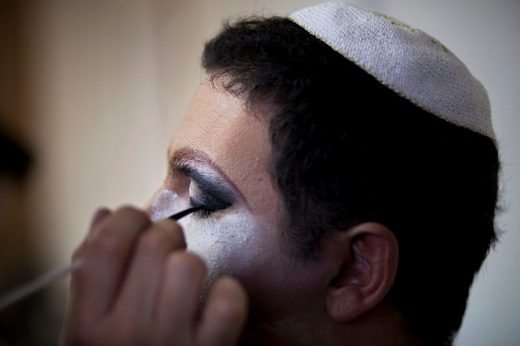 . In this photo taken on Tuesday, June 18, 2013, Israeli Orthodox Jew Shahar Hadar has his makeup applied as he prepares for a show at a drag queen school  in downtown Tel Aviv, Israel. Hadar, a telemarketer by day, has taken the gay Orthodox struggle from the synagogue to the stage, beginning to perform as one of Israel\'s few religious drag queens. His drag persona is that of a rebbetzin, a female rabbinic advisor, a wholesome guise that stands out among the sarcastic and raunchy cast of characters on Israel\'s drag queen circuit. (AP Photo/Oded Balilty)