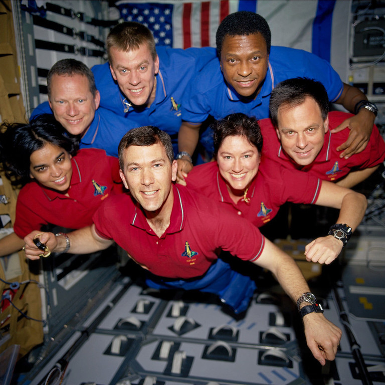 ". STS107-735-032 (16 January - 1 February 2003) --- The STS-107 crew members strike a ""flying\"" pose for their traditional in-flight crew portrait in the SPACEHAB Research Double Module (RDM) aboard the Space Shuttle Columbia. From the left (bottom row), wearing red shirts to signify their shift\'s color, are astronauts Kalpana Chawla, mission specialist; Rick D. Husband, mission commander; Laurel B. Clark, mission specialist; and Ilan Ramon, payload specialist. From the left (top row), wearing blue shirts, are astronauts David M. Brown, mission specialist; William C. McCool, pilot; and Michael P. Anderson, payload commander. Ramon represents the Israeli Space Agency. EDITOR\'S NOTE: On February 1, 2003, the seven crew members were lost with the Space Shuttle Columbia over North Texas. This picture was on a roll of unprocessed film later recovered by searchers from the debris."