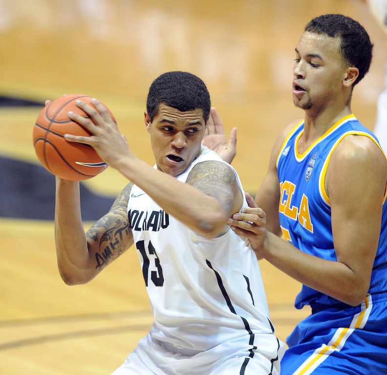 . Dustin Thomas of CU looks to make a move on Kyle Anderson of UCLA during the second half of the January 16, 2014 game in Boulder.  (Cliff Grassmick/Daily Camera)