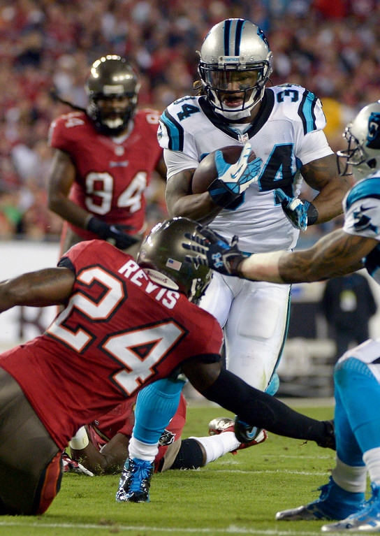 . Carolina Panthers running back DeAngelo Williams (34) gets past Tampa Bay Buccaneers cornerback Darrelle Revis (24) for a 12-yard touchdown run during the first half of an NFL football game in Tampa, Fla., Thursday, Oct. 24, 2013. (AP Photo/Phelan M. Ebenhack)