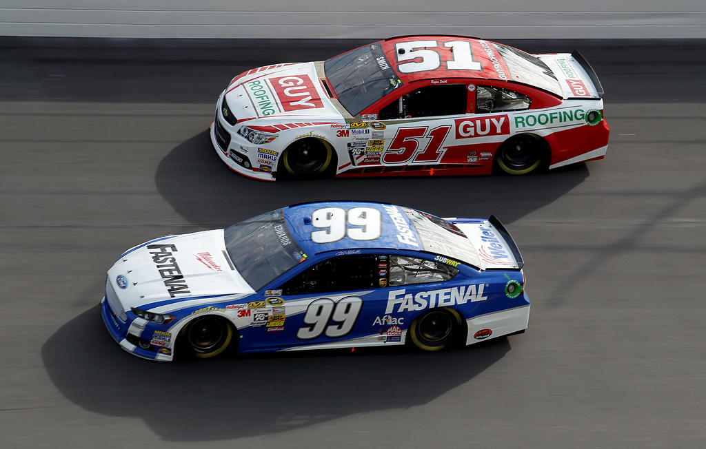 . Carl Edwards, driver of the #99 Fastenal Ford, races Regan Smith, driver of the #51 Guy Roofing Chevrolet, during the NASCAR Sprint Cup Series Budweiser Duel 1 at Daytona International Speedway on February 21, 2013 in Daytona Beach, Florida.  (Photo by Todd Warshaw/Getty Images)