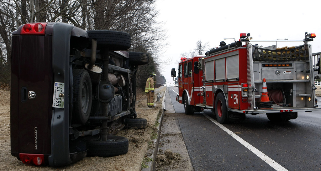 . A firefighter is seen next to a truck that turned over after skidding in Cordova, Tenn., Wednesday, Feb 12, 2014. The driver was not injured. Trees and limbs began snapping under the weight of a coat of ice in east Alabama Wednesday, blocking roads during a winter storm that forecasters said could leave as much as a foot of snow in the Tennessee Valley. (AP Photo/The Commercial Appeal, Karen Pulfer Focht)
