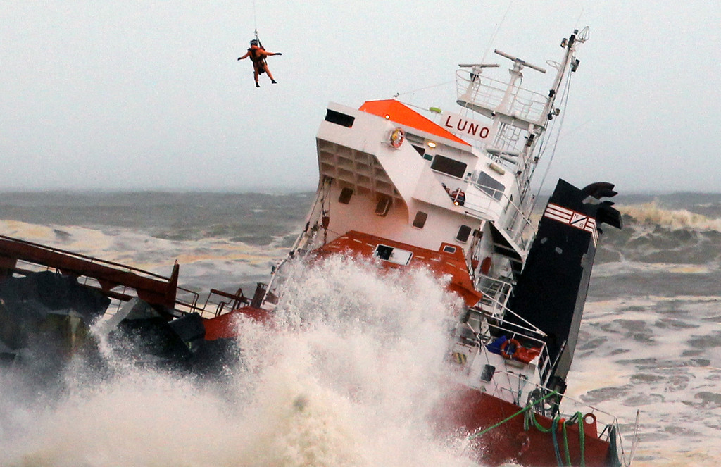 . A helicopter lowers a rescue worker toward a Spanish cargo ship the Luno that slammed into a jetty in choppy Atlantic Ocean waters off Anglet, southwestern France, Wednesday Feb. 5, 2014. The ship had been heading to a nearby port to load up with cargo when its engine failed and the rough waves carried it into the jetty. (AP Photo/Bob Edme)