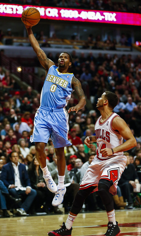 . Denver Nuggets guard Aaron Brooks launches a hook shot over Chicago Bulls guard D.J. Augustin (R) in the first half of their NBA game at the United Center in Chicago, Illinois, USA, 21 February 2014  EPA/TANNEN MAURY