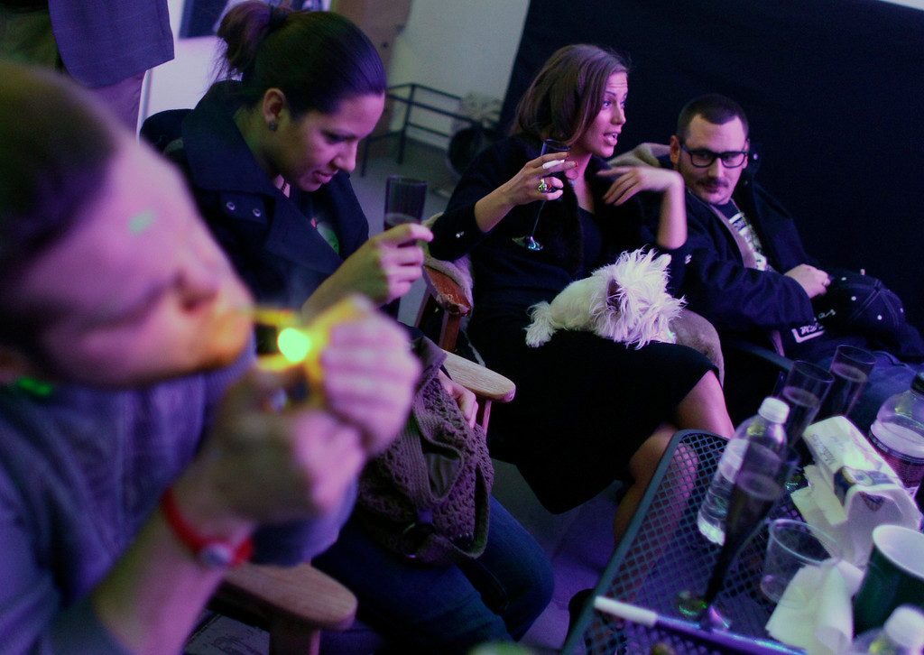 . Rachel Schaefer of Denver, second from right, and others smoke marijuana on the official opening night of Club 64, a marijuana-specific social club, where a New Year\'s Eve party was held, in Denver, Monday Dec. 31, 2012. On Election Day, Nov. 6, 2012, a plurality of Coloradans voted in favor of Proposition 64 to legalize recreational marijuana. (AP Photo/Brennan Linsley)